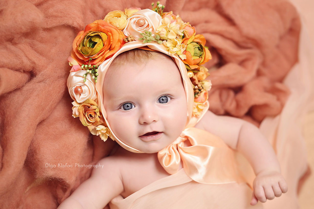 baby girl with beautiful blue eyes wearing orange floral bonnet