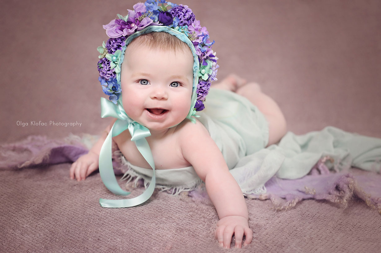 portrait of a beautiful smiling happy 5-month-old baby girl wearing purple floral bonnet