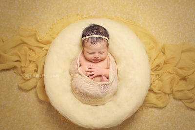 portrait of a newborn baby girl with black hair sleeping in a yellow cocoon