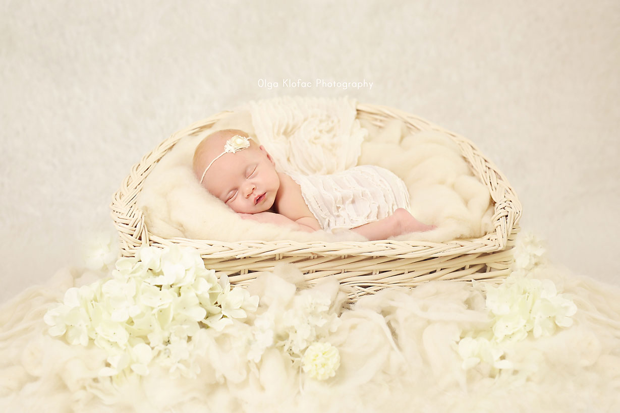 portrait of sleeping newborn baby girl with white headband on a bed of flowers