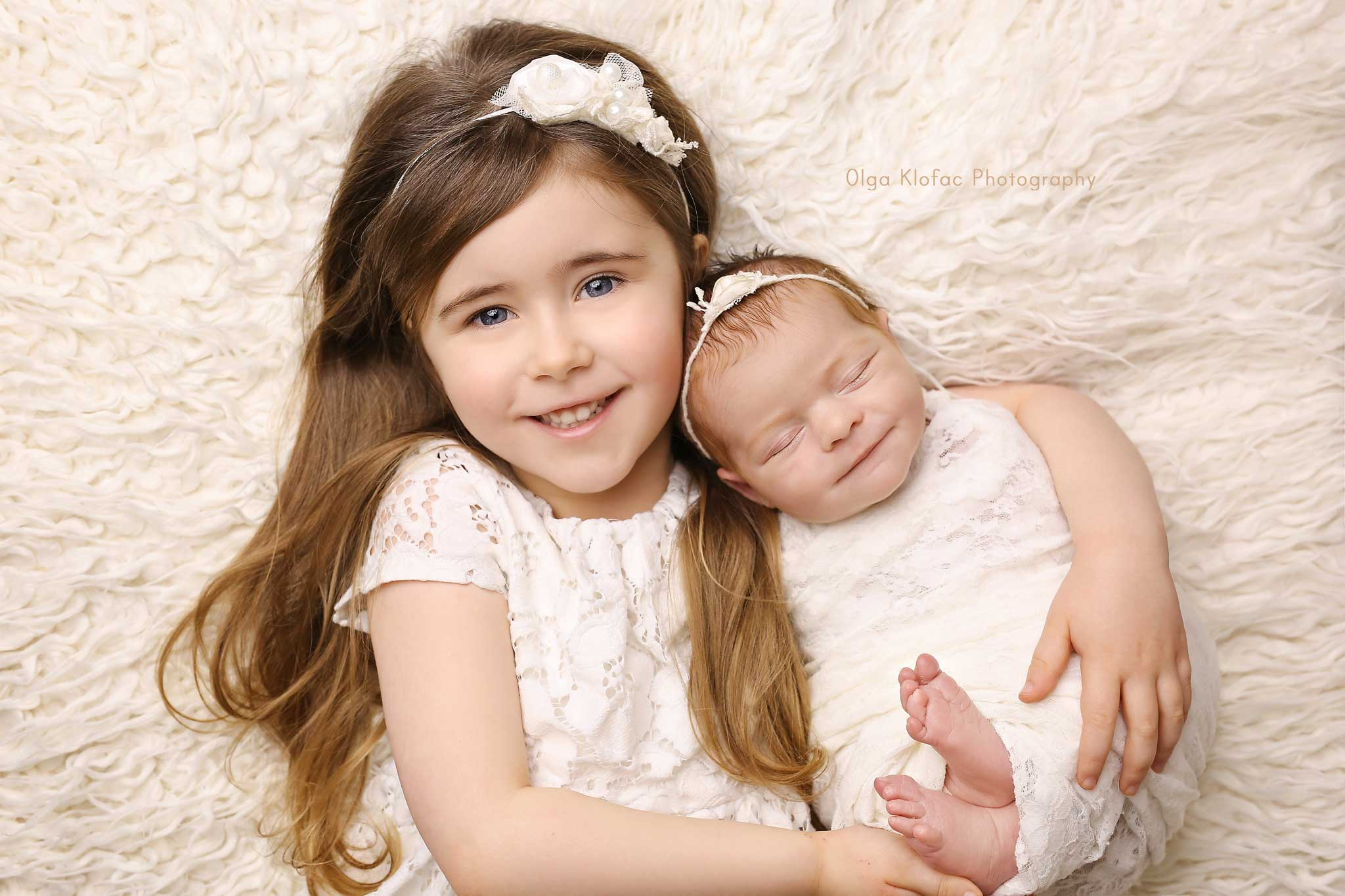beautiful photo of baby girl with her big sister taken by professional baby photographer Sligo