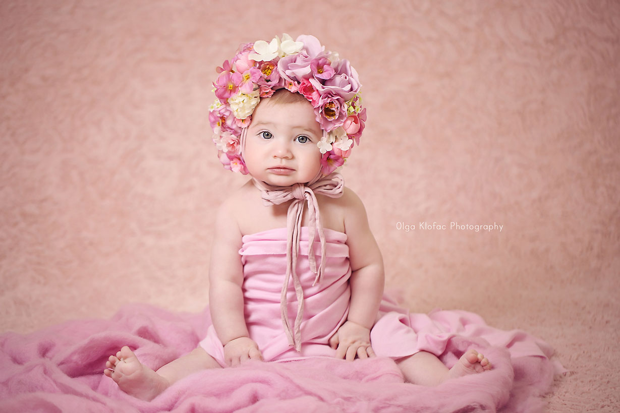 unique portrait of a beautiful 8-month-old baby girl wearing pink floral bonnet