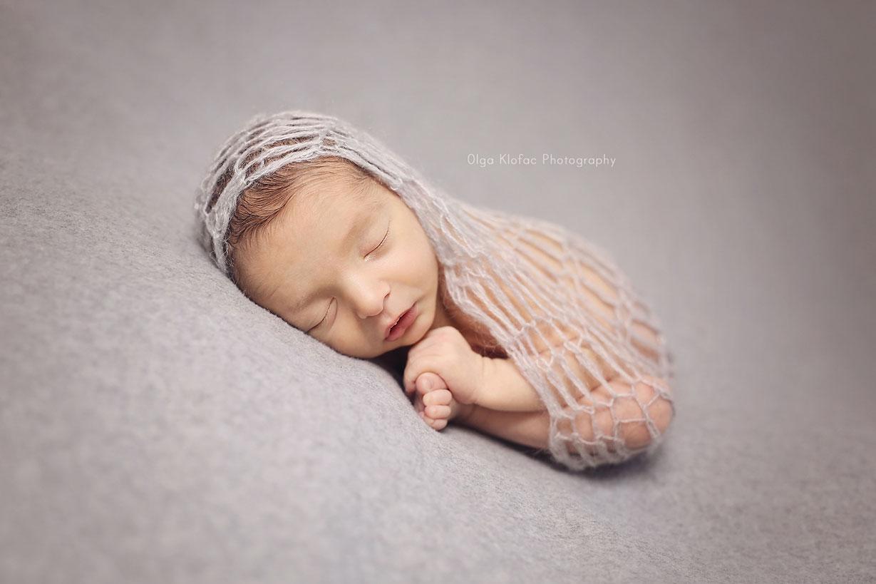 portrait of newborn baby boy sleeping on his tummy