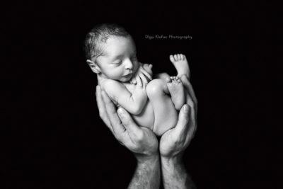 professional portrait of newborn baby boy held in his dad's hands
