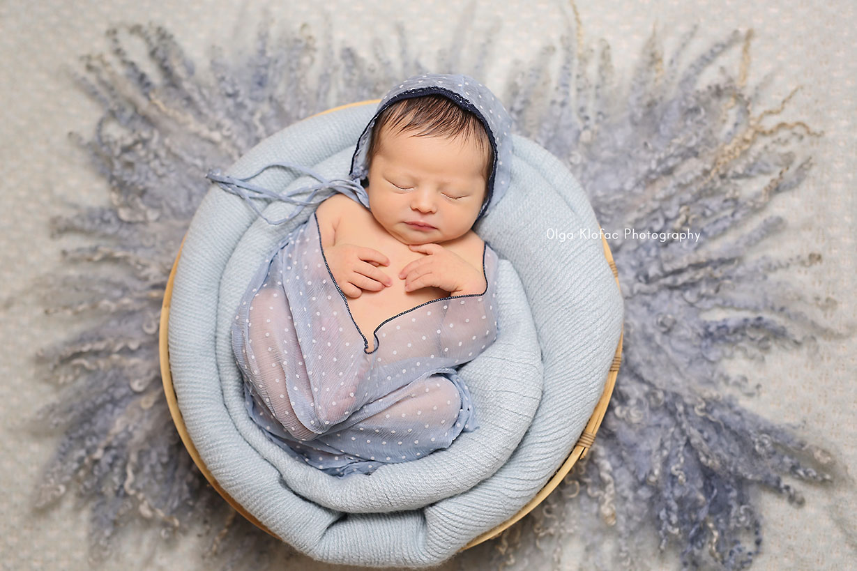 newborn baby girl with black hair sleeping in a blue basket