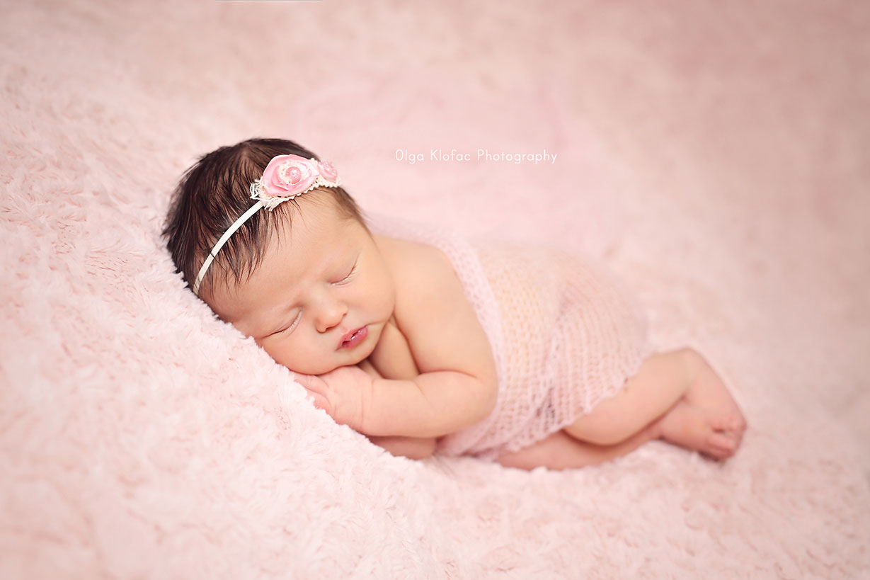 newborn baby girl with black hair sleeping on her side on a pink blanket