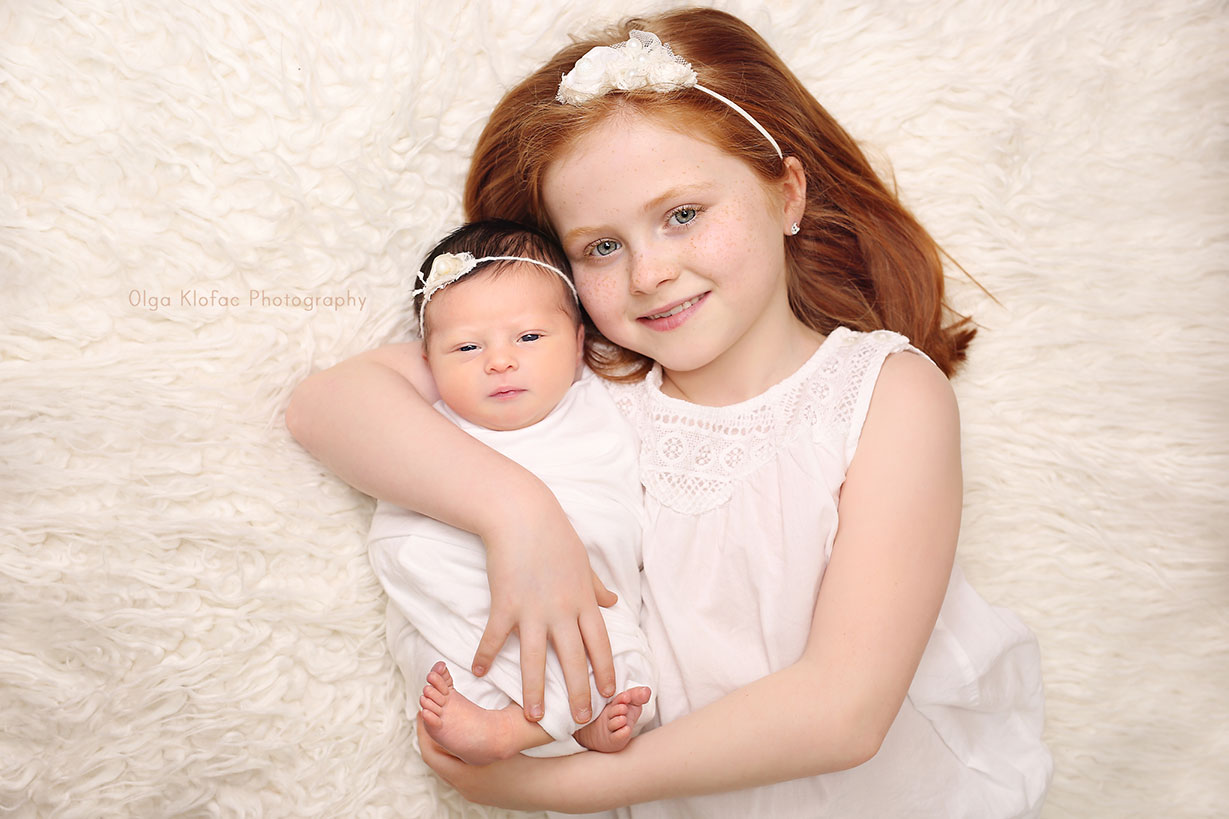 sibling photo of a newborn baby girl with black hair and her redhead sister