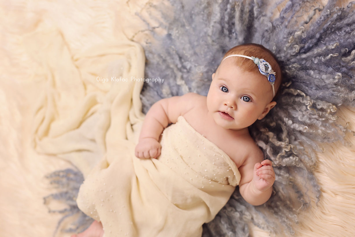 4-month-old baby girl with big blue eyes wearing blue headband and lying on a blue fur