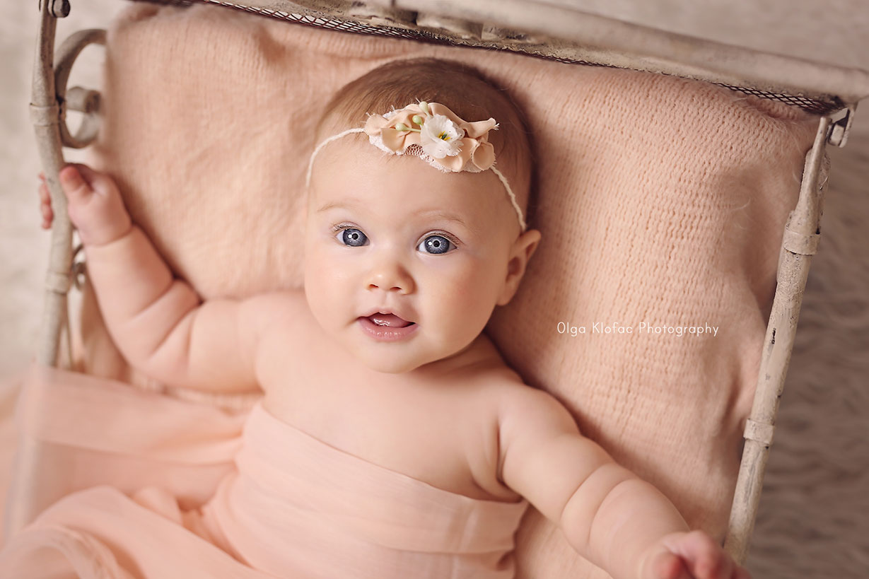 4-month-old baby girl with big blue eyes wearing peachy headband