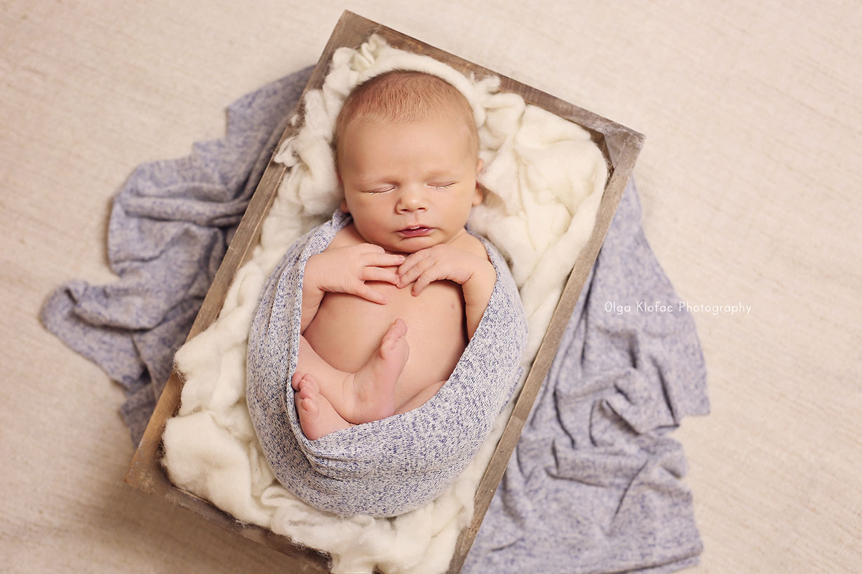 newborn baby boy sleeping in a box stuffed with soft wool