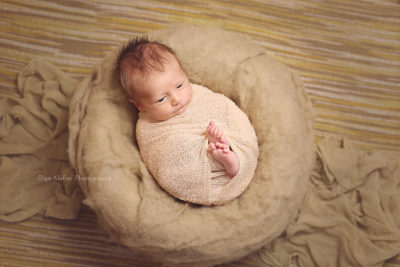 newborn boy with lots of hair lying in a cocoon