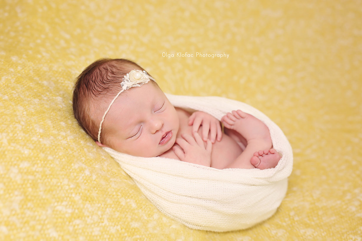 portrait of a newborn baby girl in yellow and white