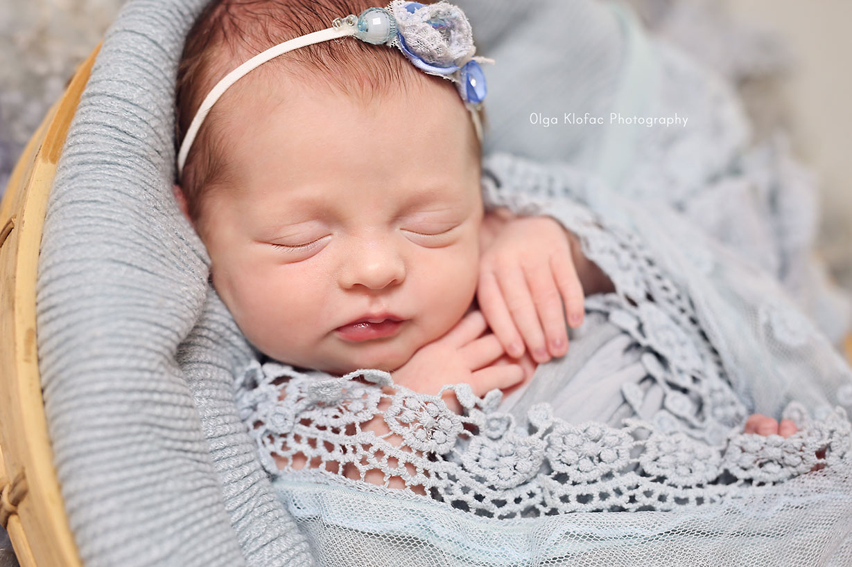newborn baby girl wrapped in blue lace sleeping in a basket