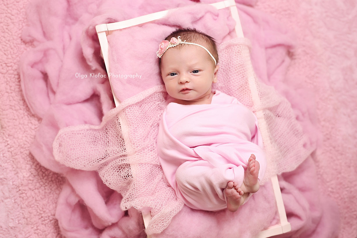 newborn baby girl wearing pink headband lying in pink cot