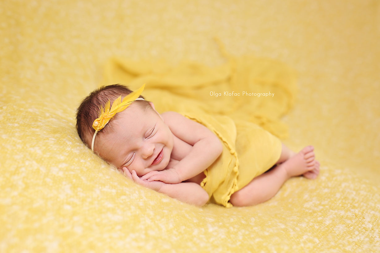 portrait of a smiling newborn baby girl in yellow