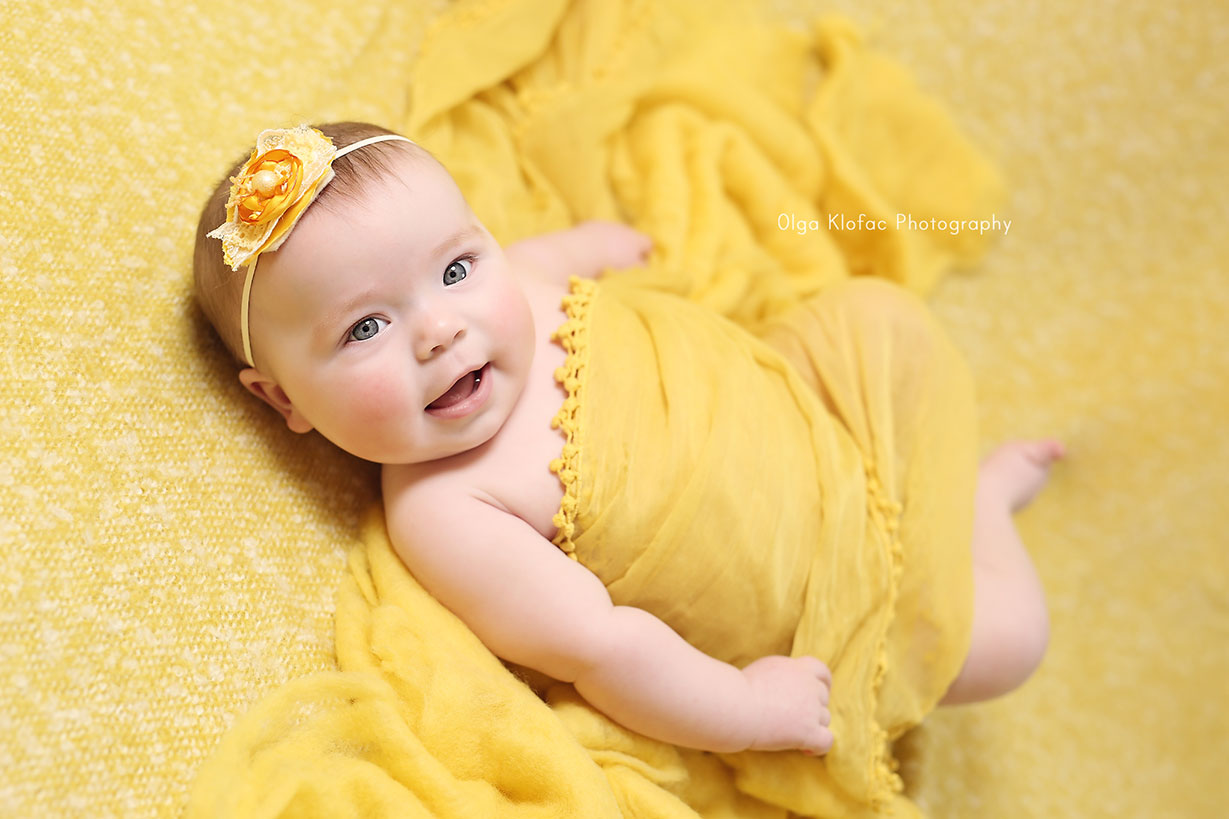 portrait of a beautiful 5-month-old baby girl smiling wearing yellow headband