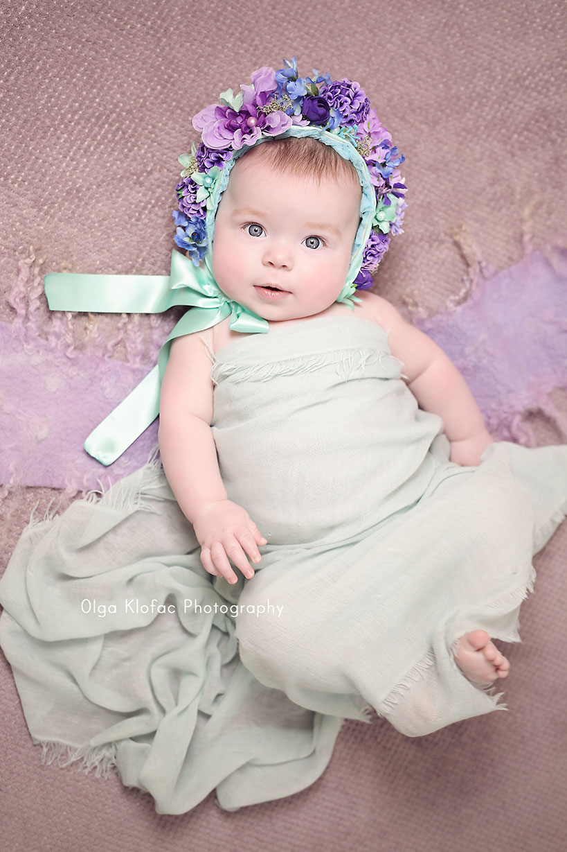portrait of a beautiful 5-month-old baby girl wearing purple floral bonnet