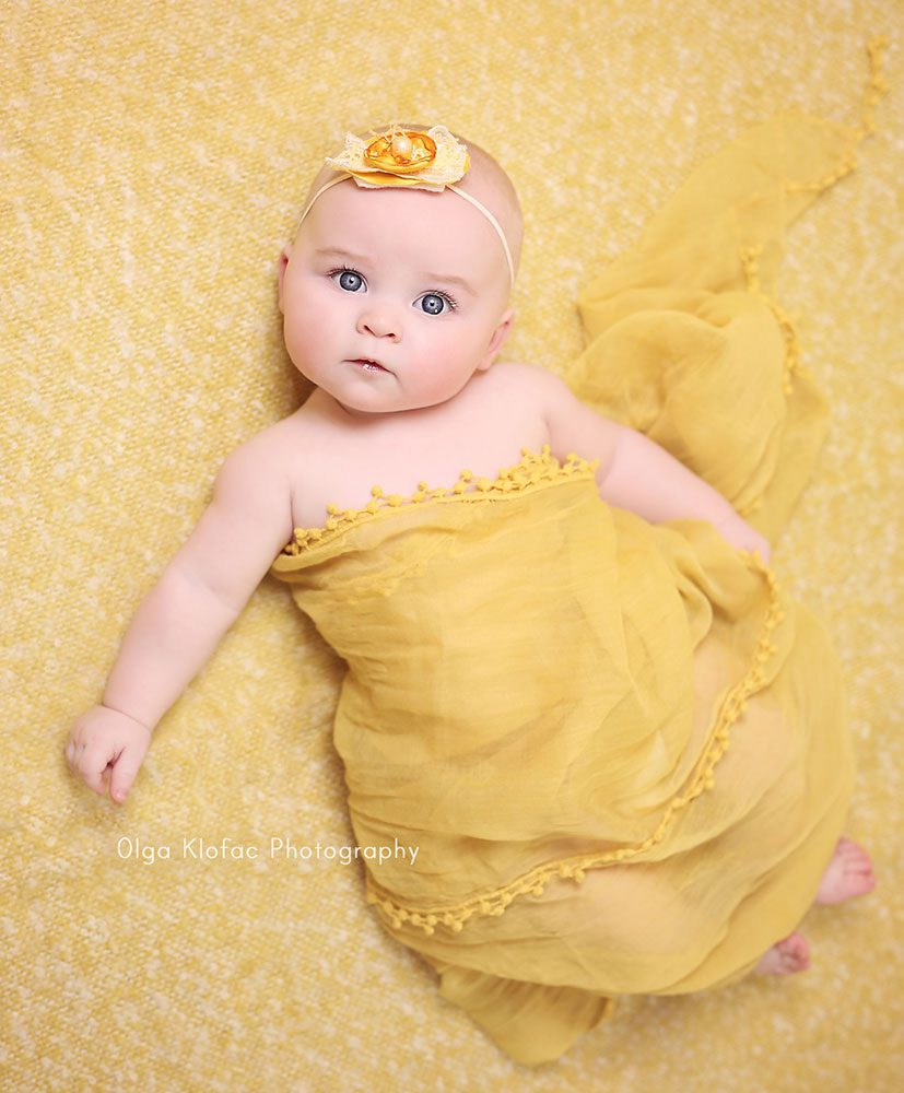beautiful 5-month-old baby girl wearing yellow headband