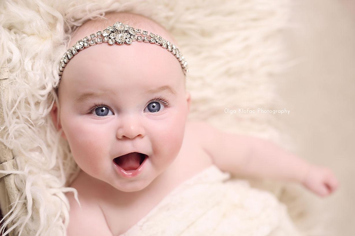 smiling 5-month-old baby girl wearing diamante headband