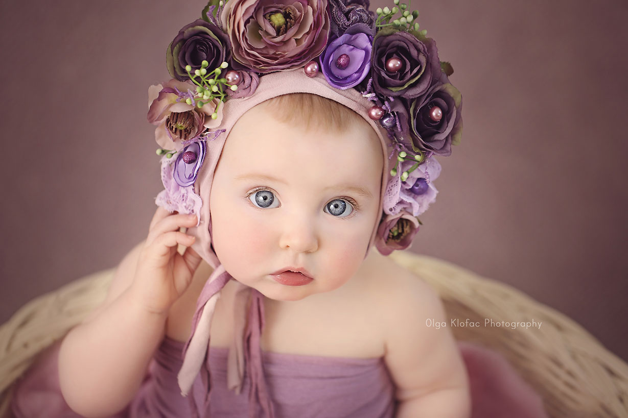 portrait of 10-month-old baby girl with purple floral bonnet
