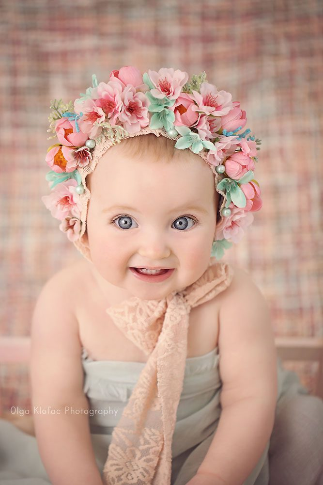 portrait of 10-month-old baby girl with pink floral bonnet