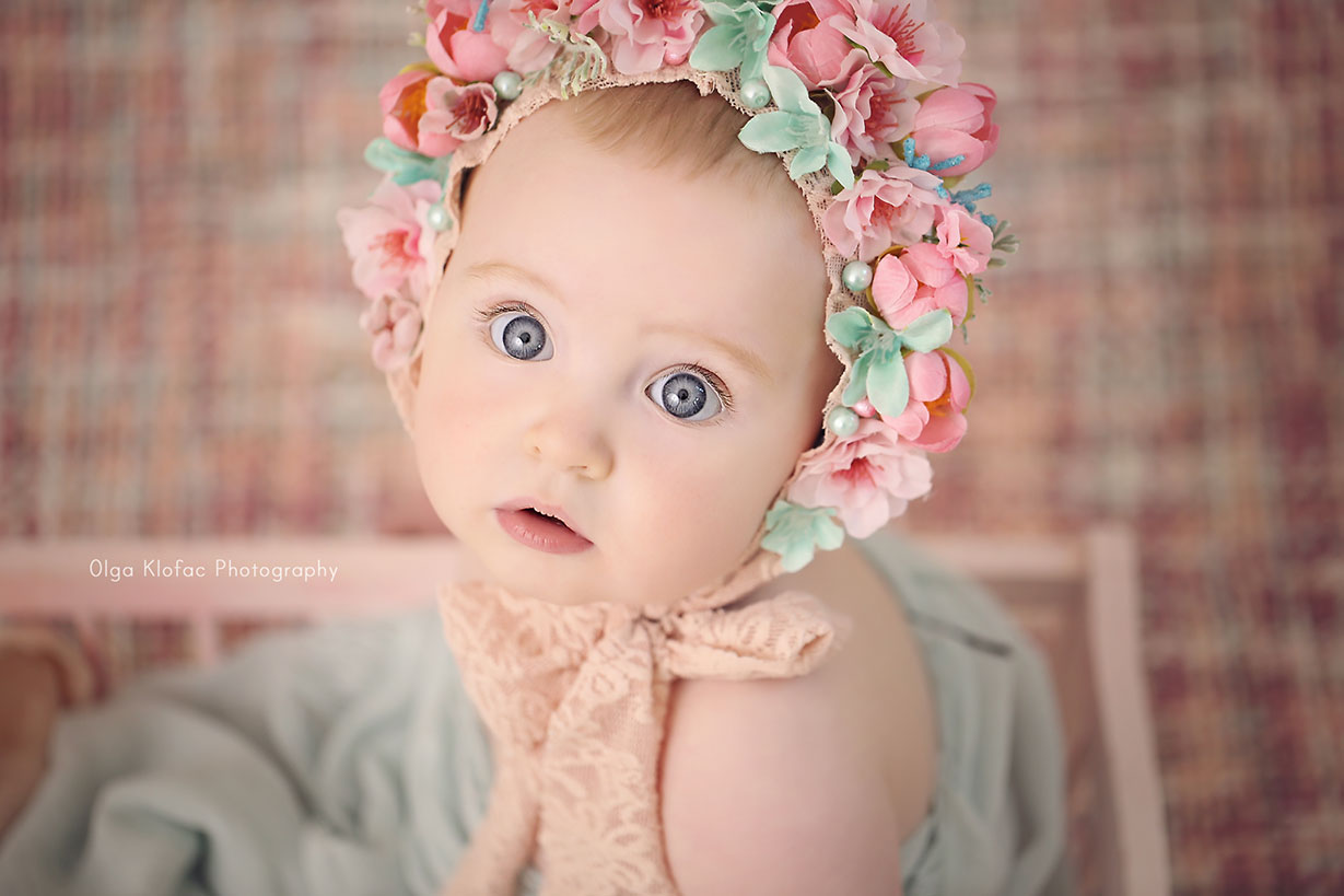 portrait of 10-month-old baby girl with big blue eyes wearing pink floral bonnet