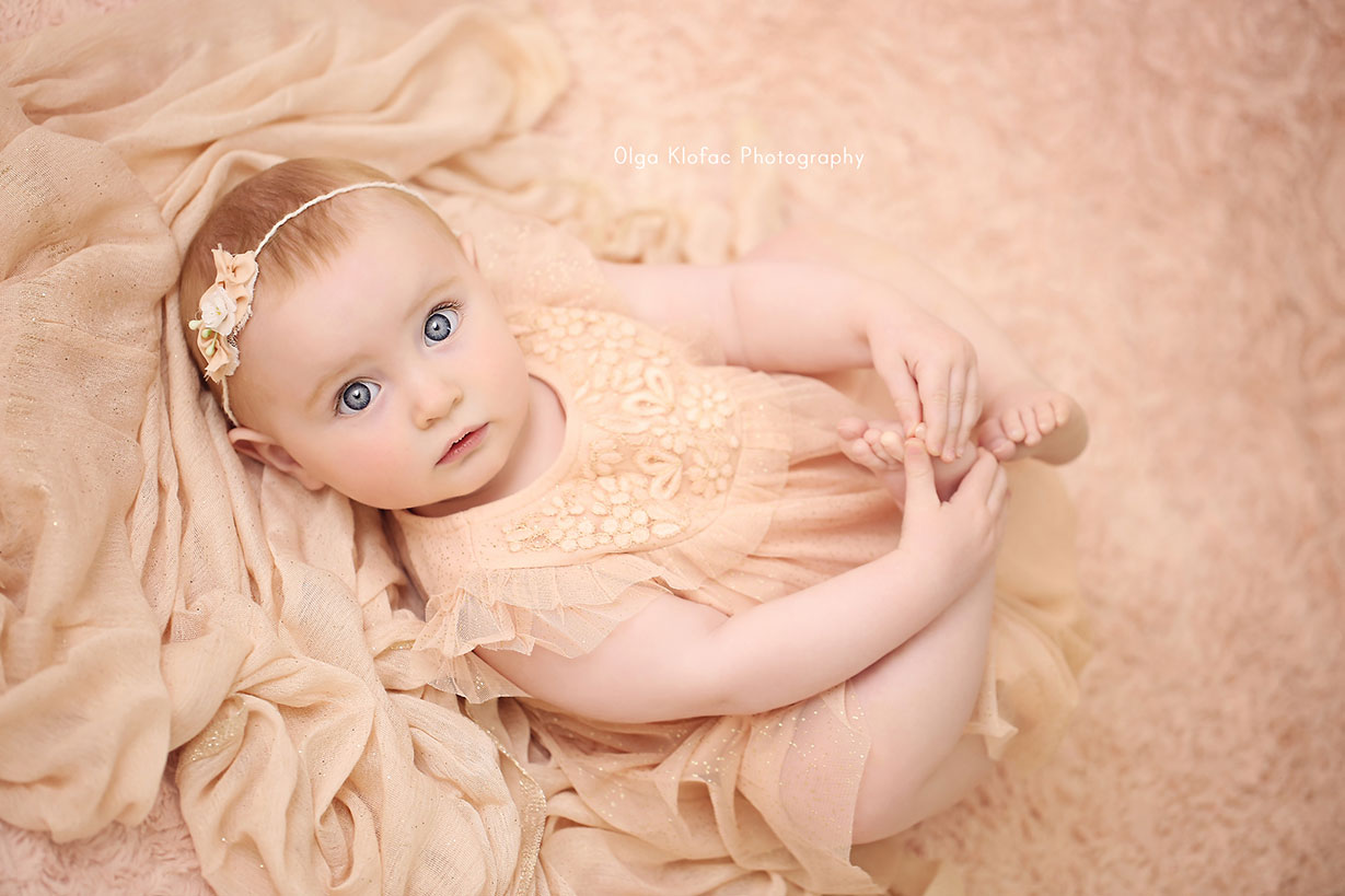 portrait of 10-month-old baby girl with big blue eyes